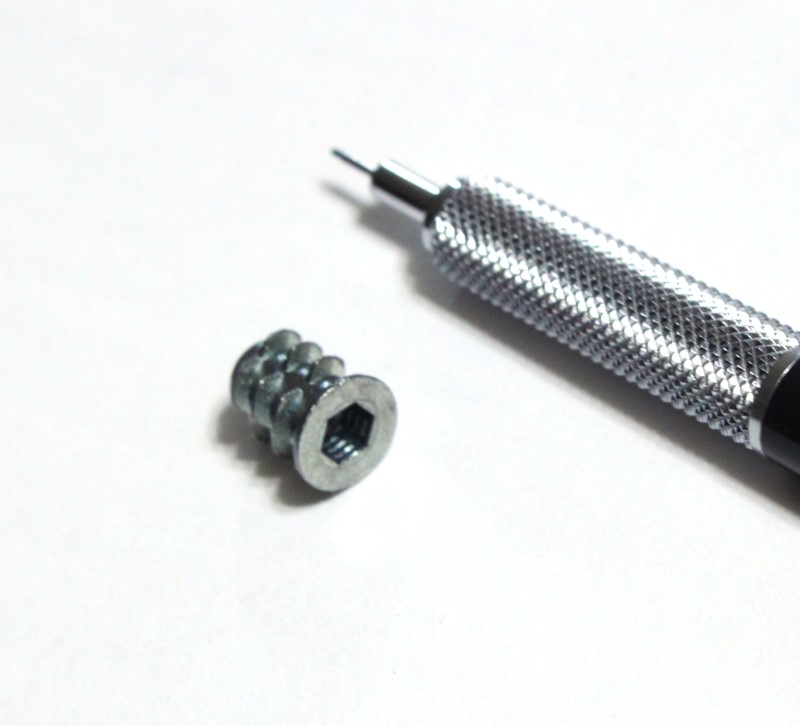 Number 8 insert nut shown with mechanical pencil for scale