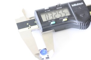LED button shown with a caliper. The measurement reads .3255 inches.