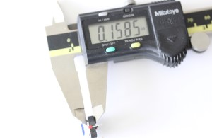 LED button shown with a caliper. The measurement reads .1585 inches.