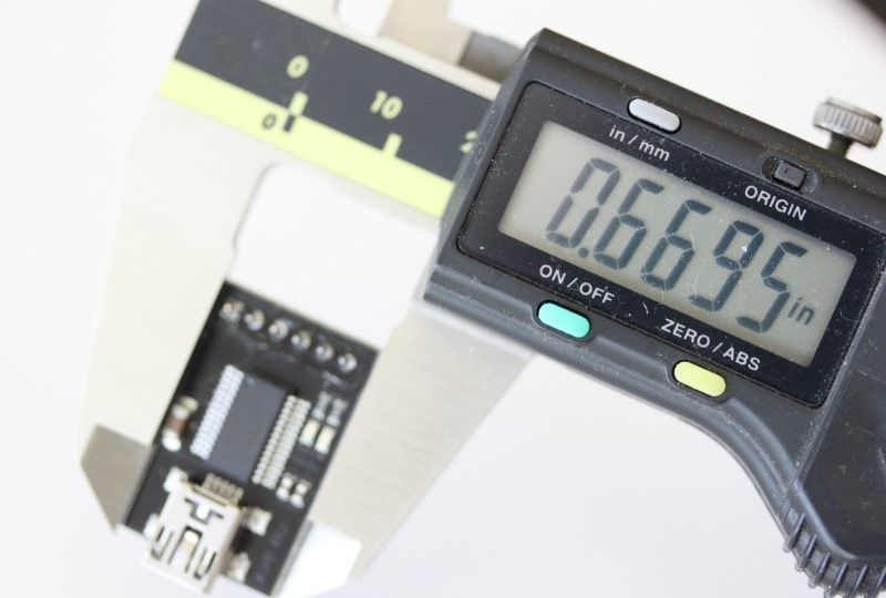 USB to serial converter shown with caliper. The measurement reads .6695 inches.