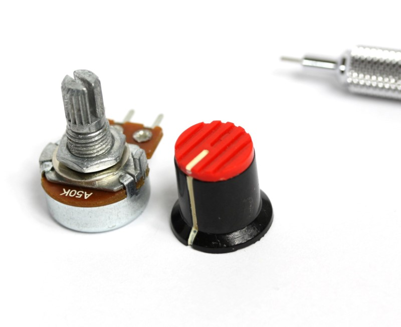 This image depicts a potentiometer and a small knob shown side by side with a pencil tip for scale.