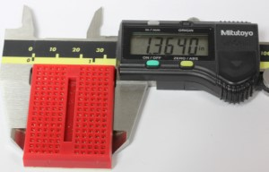 A mini breadboard inside of a caliper, showing the width.