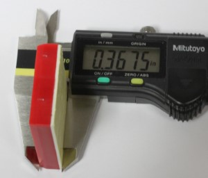 A mini breadboard in a caliper showing thickness.