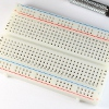 White prototyping breadboard with 30 tie strips and two power rails on each side.